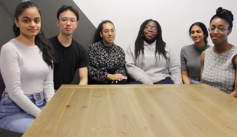 Team members Simran, Philip, Bal, Esther, Nikalya and Jocelyn sitting at a table.